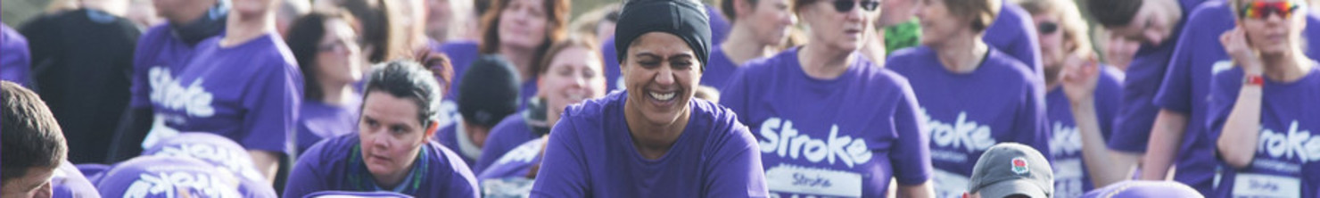 A woman in a purple t-shirt running, with a large group of people running in the background.